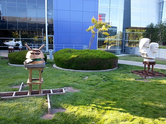 Statutes in park at the center of Google campus. Most of them are white statutes of significant people but one is not.